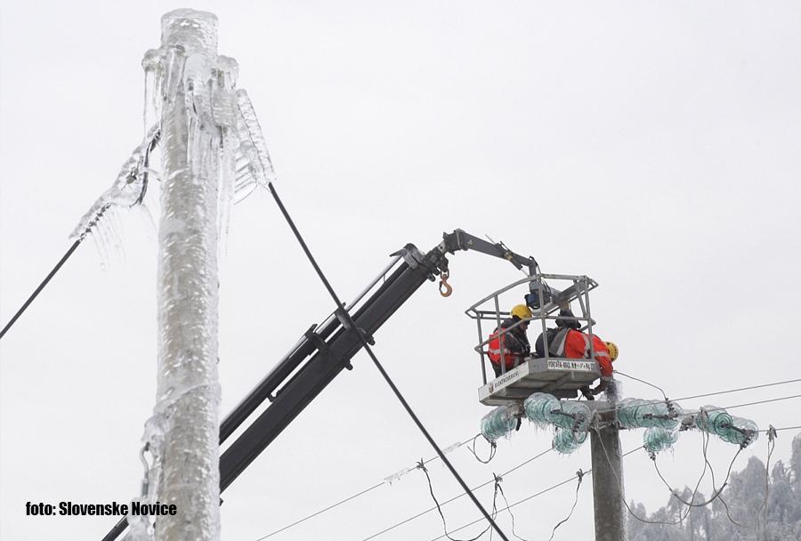 Ujma februar 2014: delavci elektro podjetja popravljajo napeljavo